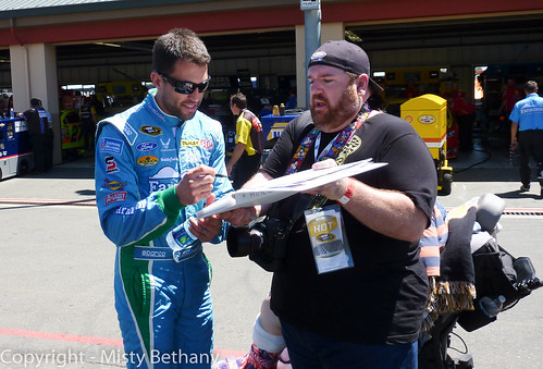 Driver Aric Almirola signs an autograph