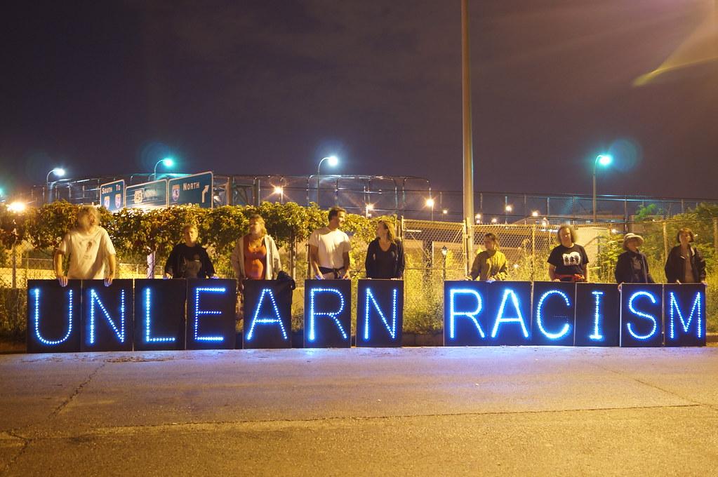 """""""unlearn racism"""" written in lights"""