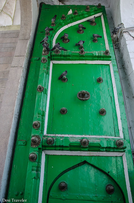 Green Gates of the Mecca Masjid with pigeons