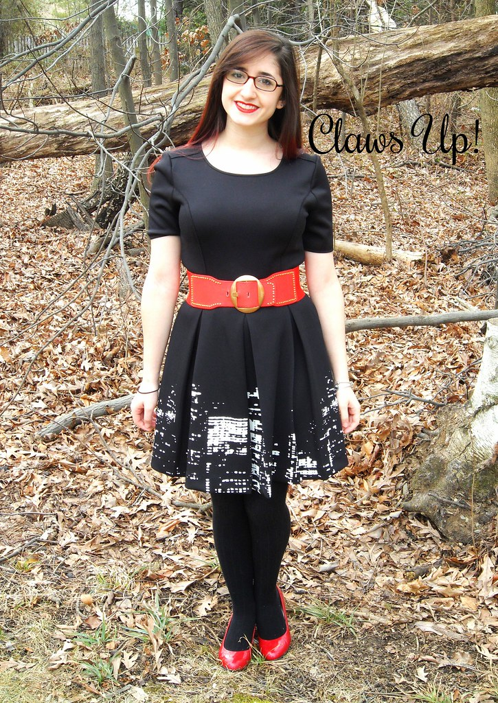 Black dress with New York City skyline print with a red belt and red heels