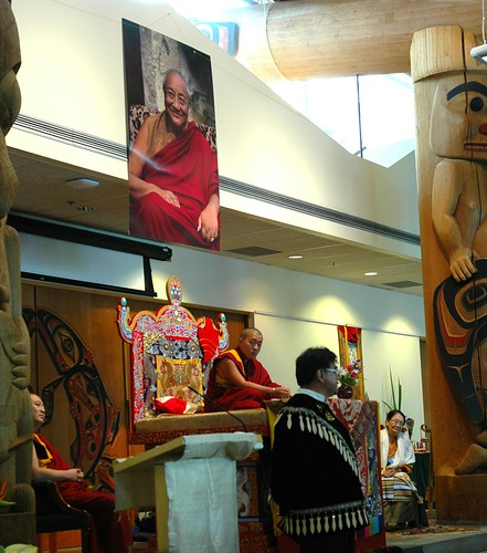 Canadian First Nations representative in traditional jacket welcomes Dilgo Khyentse Yangsi Rinpoche (on the throne) to the long house, reception for Khyentse Yangsi Rinpoche, photo of Dilgo Khyentse Rinpoche, totems, Lotus Speech, Vancouver BC, Canada by Wonderlane