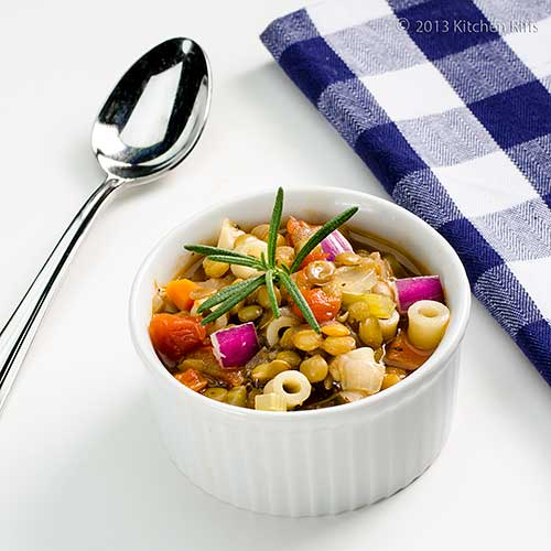 Lentil and Tomato Soup with rosemary garnish in white ramekin