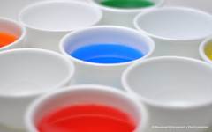 White cups, some empty, some containing multicoloured liquids