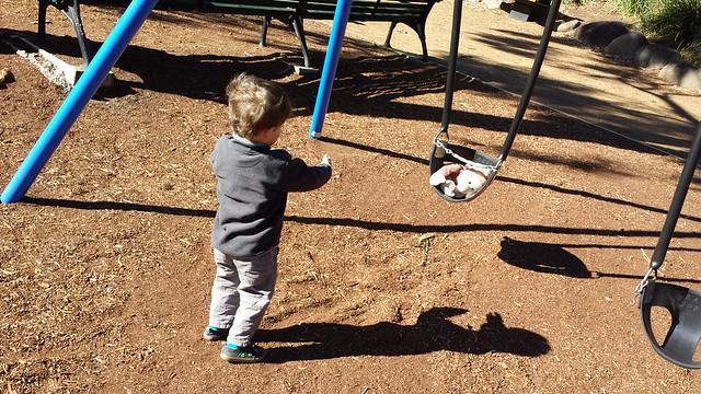 Eskil pushing Monkey on the swing