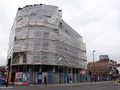 The end of a terrace, covered in scaffolding and wrappings.  To the right of this is a gap in the terrace, and further on along to the right is the continuation of the terrace, shored up with props.