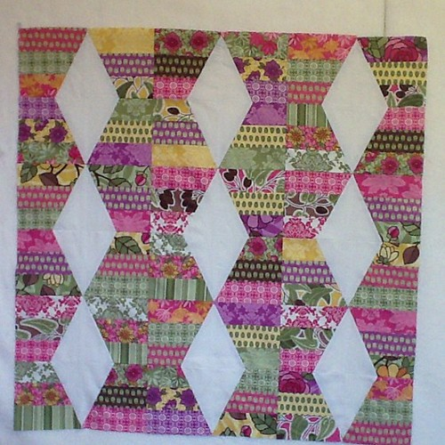 Small quilt made with half a Riley Blake jelly roll and the lazy angle ruler