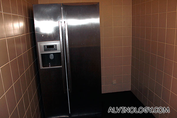 Giant fridge tucked in a corner as it's modern appearance do not gel so well with the overall interior design