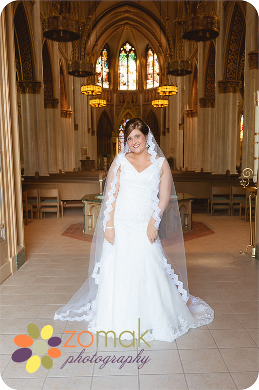 Beautiful bride stands in the doorway to the St helena Cathedral just before seeing her groom on their wedding day