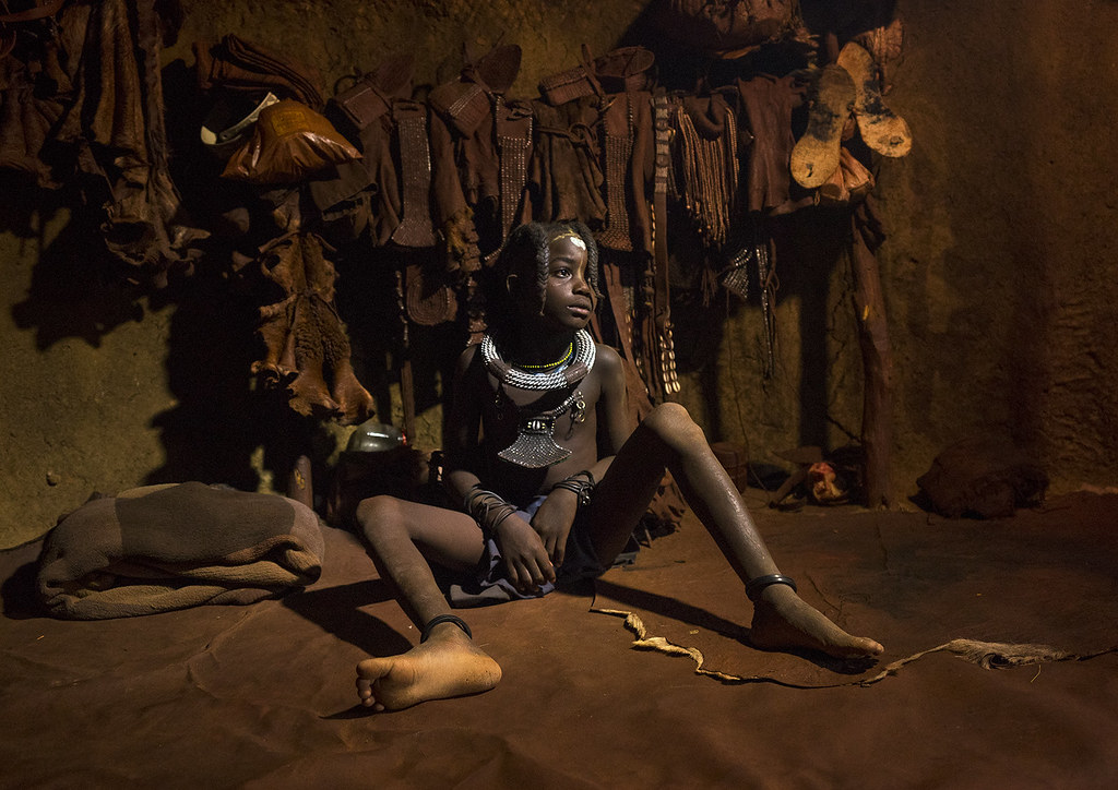 Young Himba Girl With Ethnic Hairstyle In Her Bedroom hut, Epupa, Namibia
