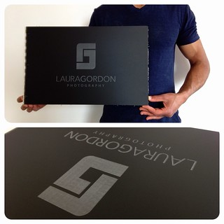 Custom photography portfolio book in matte black acrylic with engraving treatment