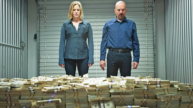 Skyler and Walt look down at a giant pile of money