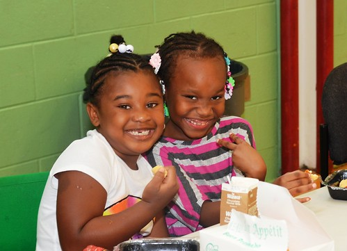 Two little girls enjoy a nutritious meal at one of the Philadelphia Archdiocese's Nutritional Development Services 450 summer food service sites.