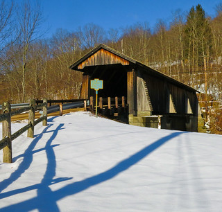 Long Shadows In Front Of A Covered Bridge