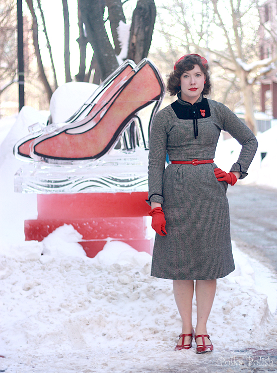 Posing next to an ice sculpure of red high heels wearing red shoes, gloves, and hat with a black and white wool dress