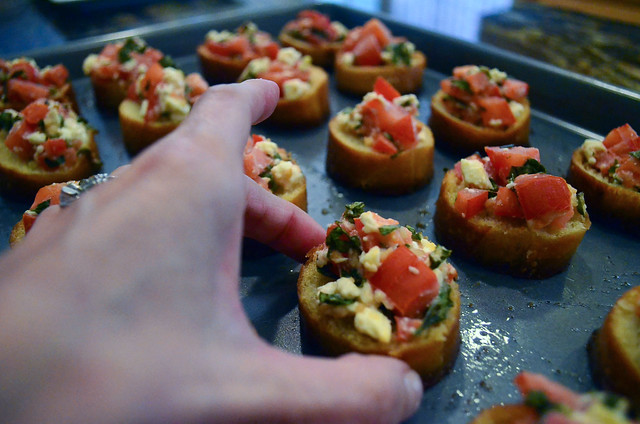 The completed Feta Bruschetta with a hand grabbing one of them.