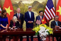 Peace Corps Director Carrie Hessler-Radelet signs a historic partnership to establish a Peace Corps program for the first time in Vietnam, as U.S. Secretary of State John Kerry and U.S. Ambassador to Vietnam Ted Osius stand behind her, at the Ministry of Foreign Affairs in Hanoi, Vietnam, May 24, 2016. The announcement of the partnership coincides with U.S. President Barack Obama's trip to Vietnam and underscores the United States' broader commitment to supporting the people of Vietnam through English language learning. [State Department photo/ Public Domain]