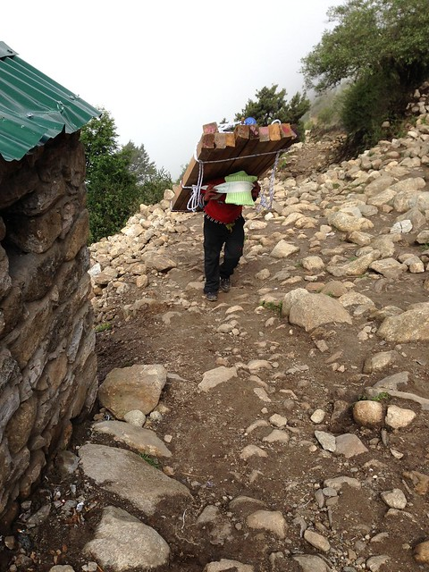 A Sherpa man and his heavy load on the Everest Base Camp trail