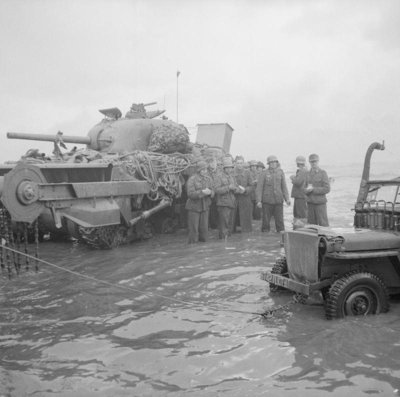 A group of German prisoners standing in the water next to a disabled Sherman Crab flail tank watch as a jeep is towed from the sea, Queen beach, Sword area, 6 June 1944.
