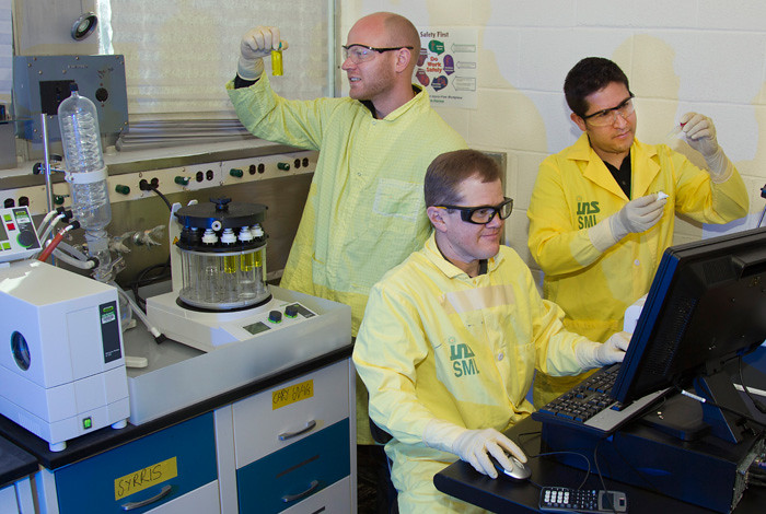 From left, Los Alamos scientists Roy Copping, Sean Reilly, and Daniel Rios.  Copping examines the Buchi Multivapor P-12 Evaporator, and Reilly and Rios are at the Agilent Technologies Cary 60 UV-Vis Spectrometer.