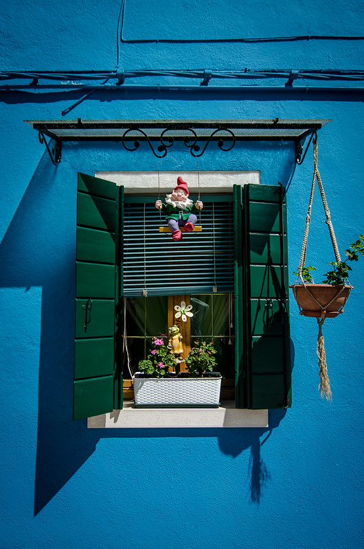 A colorful gnome hangs from a Burano window.