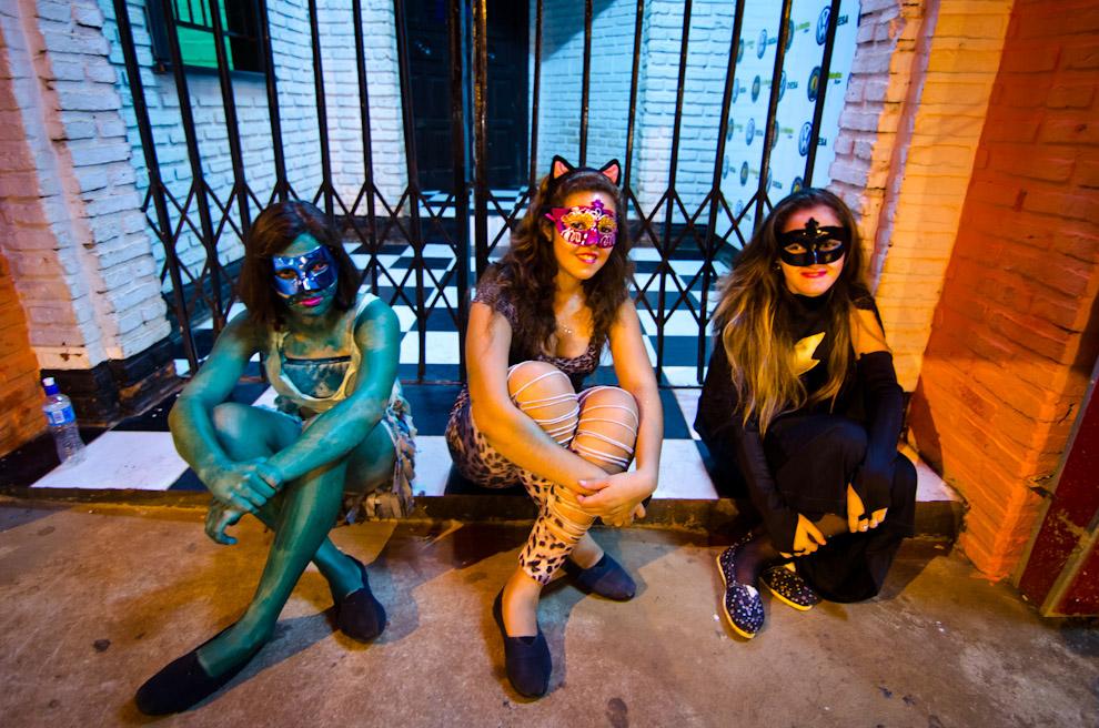 Participantes de los Corsos Encarnacenos esperan afuera de un club nocturno vestidas con trajes de súper héroes y villanos. (Elton Núñez)