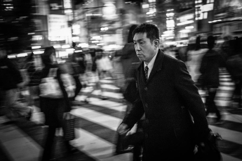 Man crossing the street at Shibuya. In Tokyo, everyone walks fast, and the pace of life does not slow down even at night.