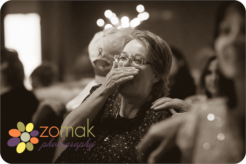 emotional mother of the groom reacts to slideshow at wedding reception