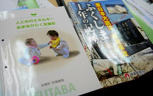 福島核電廠的文宣與核災慘狀照片集相對照,相當諷刺。