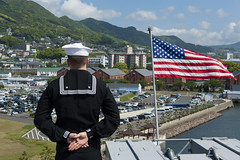 Information Systems Technician 2nd Class Aaron Becker mans the rails as USS Bonhomme Richard (LHD 6) returns to Sasebo. (U.S. Navy/MC2  Adam D. Wainwright)
