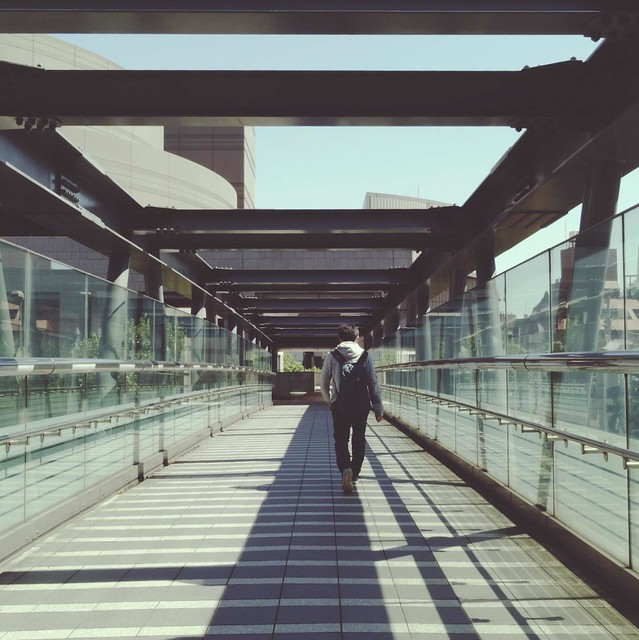 Young man walking footbridge