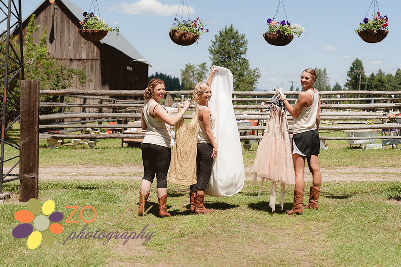 Candid shot of the bridesmaids carrying the wedding gown to the barn for detail shots