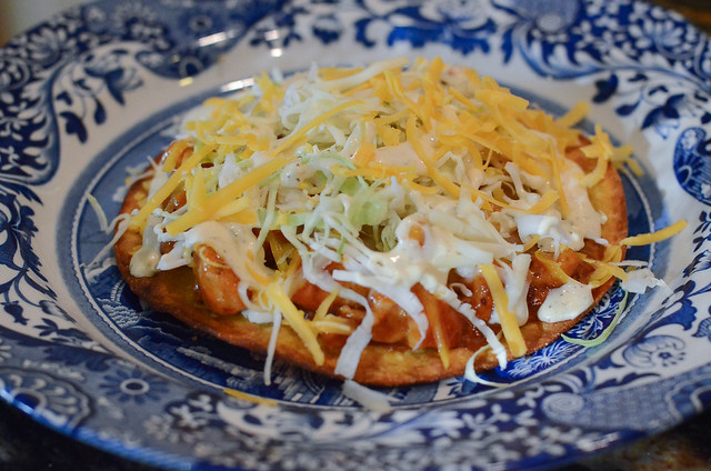 A close up of BBQ Chicken Tostada on a blue and white plate.
