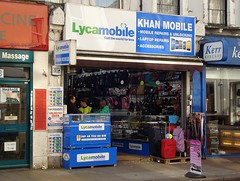 "A terraced shop with a fully open front. A counter advertising Lycamobile is to the left, with three people facing each other across it. On the right is a display of suitcases. A pink A-board stands on the pavement outside. Bags and baseball caps are visible along a wall inside the shop. Above the frontage is a blue-and-white sign with ""Lycamobile / Call the world for less"" on the left side and ""Khan Mobile / Mobile Repairs & Unlocking / Laptop Repairs / Accessories"" on the right side."