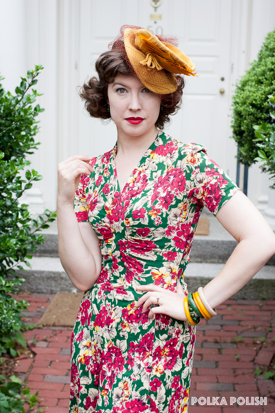 Late 30s or early 40s rayon jersey in an eye-popping floral print of cream, grey, black red, yellow, and forest green, paired with a small golden yellow tilt hat