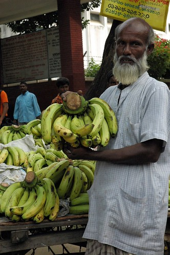 White bearded banana salesman, cart, public market, bystanders, outside Dhaka, Bangladesh by Wonderlane
