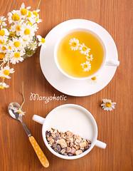 Muesli mix with yogurt in a bowl and chamomile tea