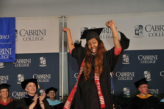 A graduate student celebrating at Commencement