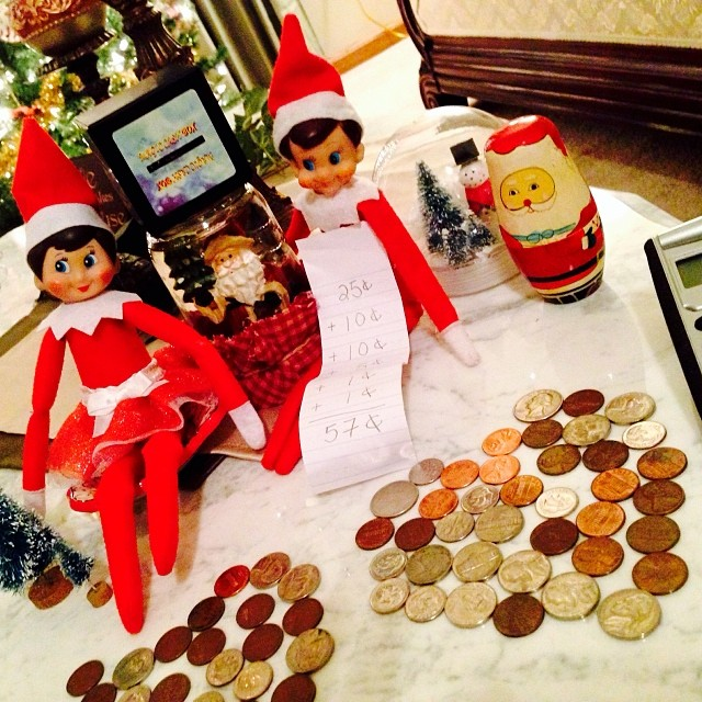 Elfie and Samantha Elf are back home from being at Grandma's for part of this week... The elves decided to play with the kids piggy bank money and made two hearts out of the coins. Elfie even got out the calculator and added up some coins. #hisugarplumelf