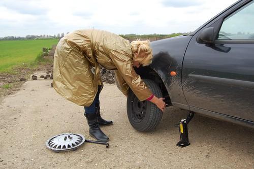 Женщина самостоятельно меняет проколотое колесо на своем автомобиле.