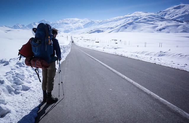 hiking with a backpack alongside a road with snow and mountains all around