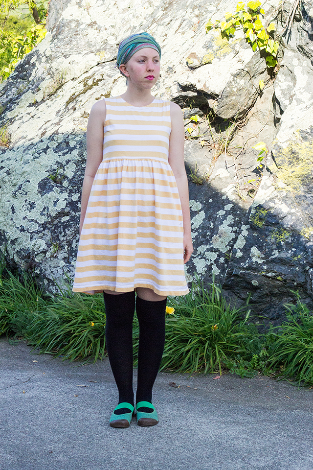 green headscarf, striped yellow dress, black knee socks