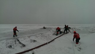 Coast Guard crew members from Station Calumet Harbor and first responders from the Chicago Fire Department rescue a man from Lake Michigan, Jan. 2, 2014. Both agencies worked together to safely remove the man from the ice who was then transferred to a local hospital. (Coast Guard photo by Petty Officer 2nd Class John Palmer)