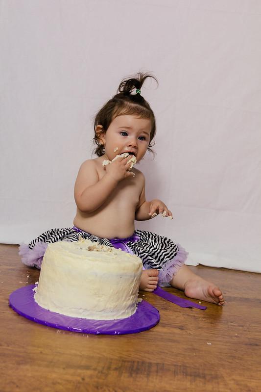 little girl in zebra pettiskirt eating icing from smash cake