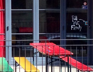 Red green and yellow cafe, downtown Wellington with quirky sign on door