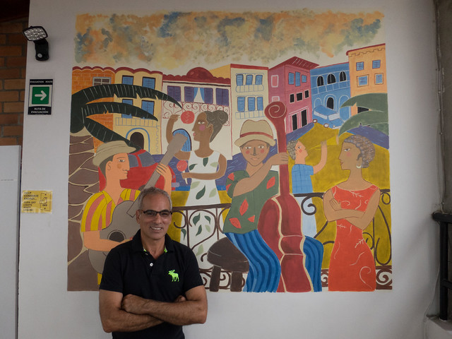 Joel, the owner, in front of a painting by one of his guests
