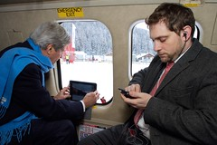 U.S. Secretary of State John Kerry, seated across from Deputy Chief of Staff Jon Finer, prepares his iPad to videotape his departure in a Swiss Air Force helicopter as he prepares to fly from the World Economic Summit in Davos, Switzerland, to Zurich, Switzerland, on January 24, 2015. [State Department Photo/Public Domain]
