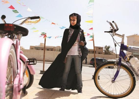 Wadjda, a young girl wearing a niqab, stares at a bike