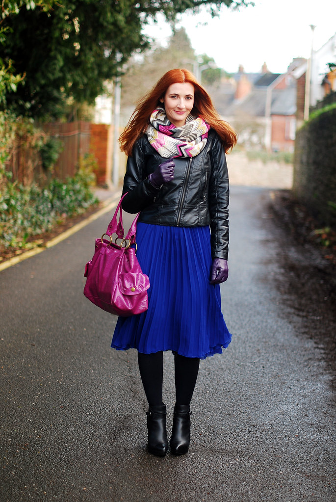 Black leather jacket and blue pleated skirt