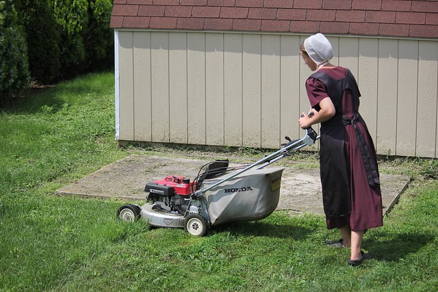 Picture of a young Amish woman pushing a Victa lawn mower