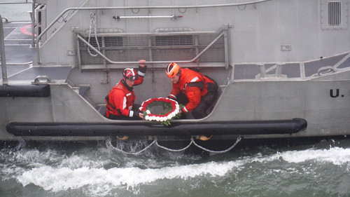 Two crew members assigned to Coast Guard Station Quillayute River in La Push, Wash., lay a wreath into the water from a 47-foot Motor Life Boat in honor of three crew members who lost their lives during a rescue mission on Feb. 12, 1997. The crew holds a memorial ceremony every year on the anniversary of the incident. (U.S. Coast Guard photo courtesy of Coast Guard Station Quillayute River)